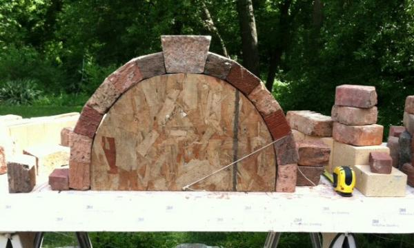 My first ever arch.  Recycled brick and granite. I'm considering having something carved in the keystone, and I have to figure out a way to give those cut edges more texture.  I hammered on it a while with other granite last night, that might work for me...learning process for sure!