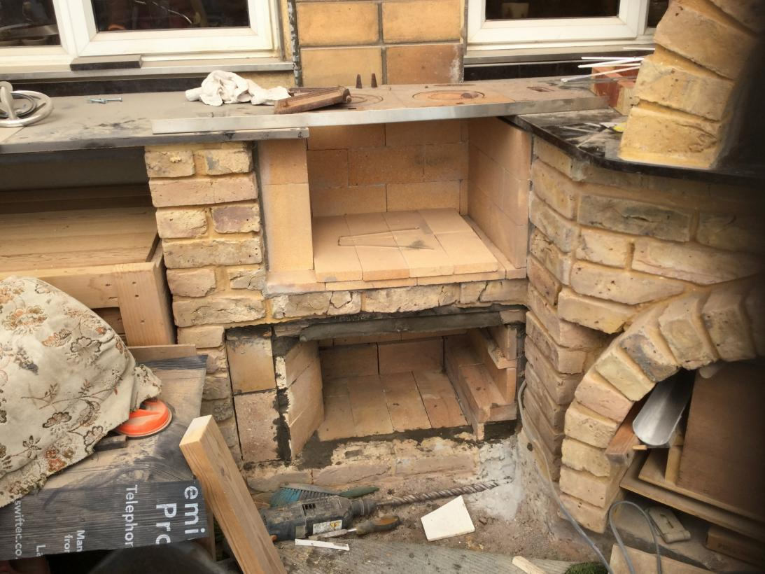 Cemented in fire bricks under grill area to take stainless steel 400mmx400mm racks old range door to go on front with a smoke pipe to send smoke up and over top grill area